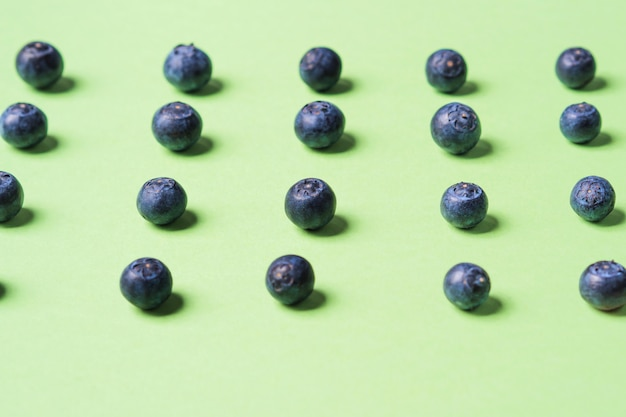 Pattern of fresh blueberries on pastel green