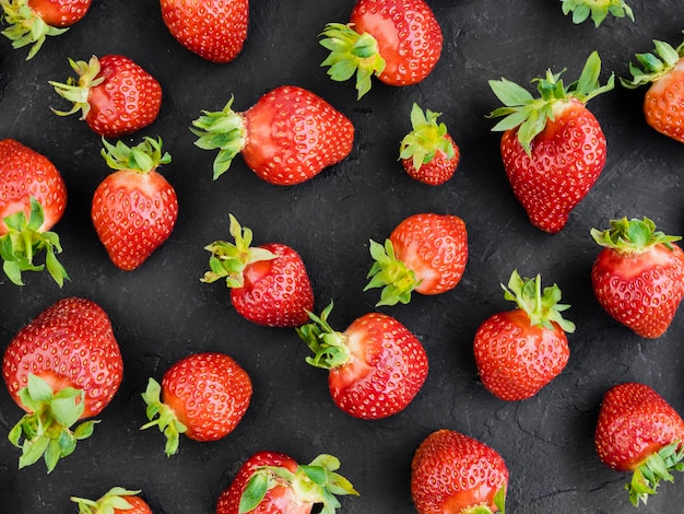 Pattern of fresh strawberries on dark surface