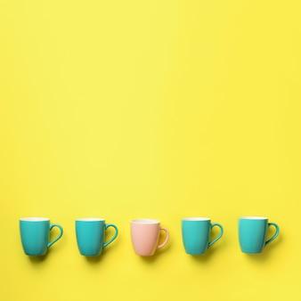 黄色の背景に青とピンクのカップからのパターン。スクエアクロップ誕生日パーティーのお祝い、ベビーシャワーのコンセプト。