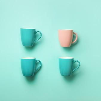 青い背景上の青いカップからのパターン。スクエアクロップ誕生日パーティーのお祝い、ベビーシャワーのコンセプト。パンチの効いたパステルカラー。ミニマリストスタイルのデザイン