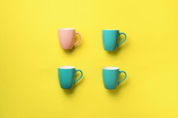 黄色の背景上の青いカップからのパターン。誕生日パーティーのお祝い、ベビーシャワーのコンセプト。パンチの効いたパステルカラー。ミニマリストスタイルのデザイン