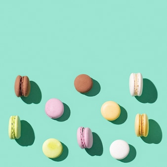 Pattern from different cake macaroons on bright blue green
