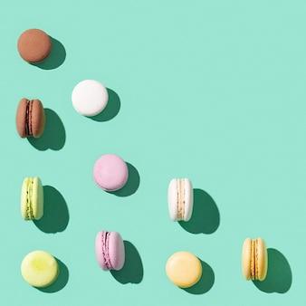 밝은 파란색 녹색 배경, 멀티 컬러 프랑스 비스킷 마카롱에 다른 케이크 마카롱에서 패턴. 달콤한 맛있는 휴가 음식.