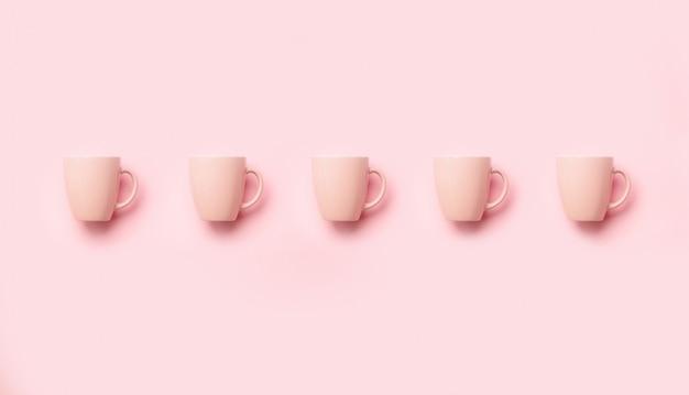 パンチのある背景の上のピンクのカップからのパターン。誕生日パーティーのお祝い、ベビーシャワーのコンセプト。ミニマリストスタイルのデザイン