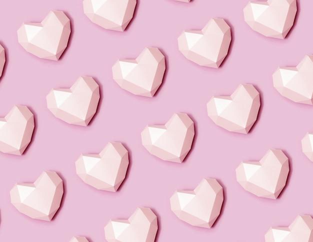 ピンクの多角形の紙のハートのパターン。