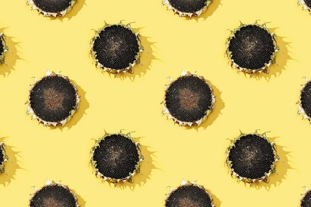黄色い紙に黒い種子と熟したヒマワリのパターン