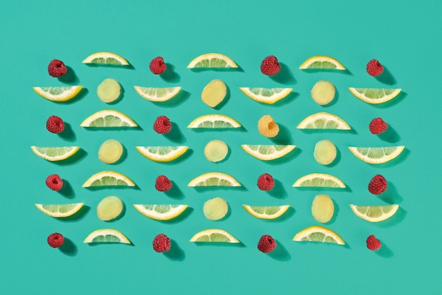 Pattern of fruit pieces of lemon and raspberry on a blue background. food background. flat lay