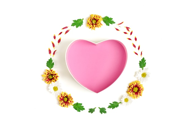 Pattern of gift box shape of heart, flowers yellow, red, white asters, green leaves  isolated on white