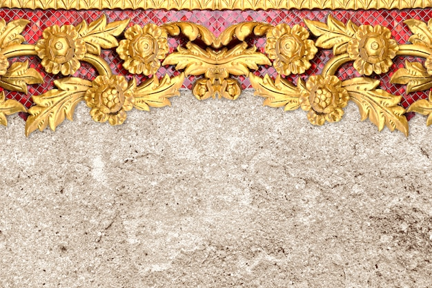Pattern of gold flowers carved on cement wall