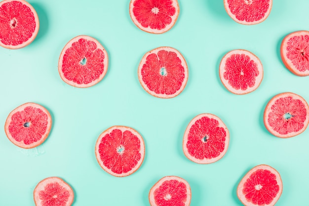 Pattern of grapefruit citrus slices on pastel backdrop