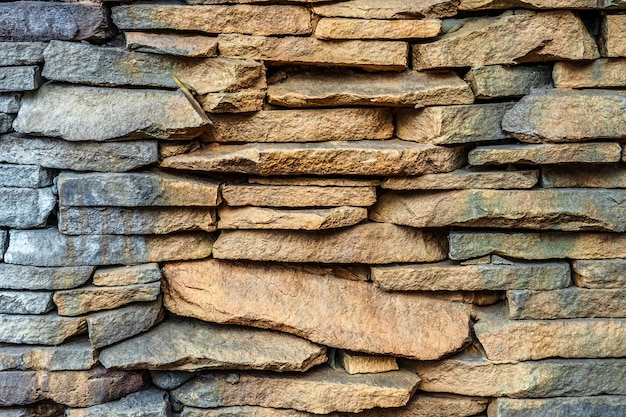 モダンなスタイルのデザイン装飾的なひびの入った本物の石壁の表面のパターングレー色