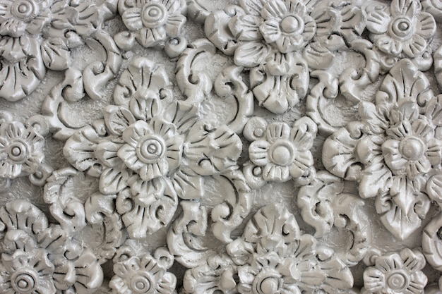 Pattern of gray flower carved on stucco design of native wall