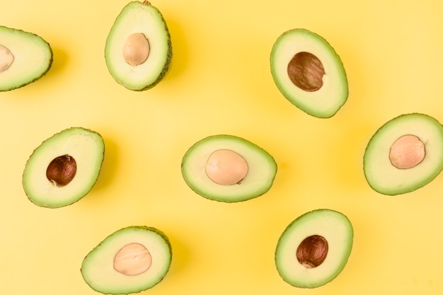 Pattern of halved avocado with seeds on yellow backdrop