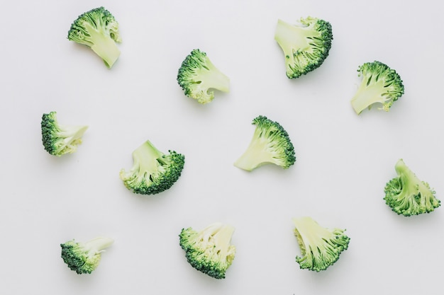 Pattern of halved cut broccoli pieces on white backdrop