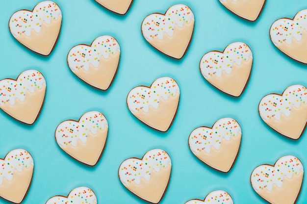 Pattern of heart shape cookies on blue background