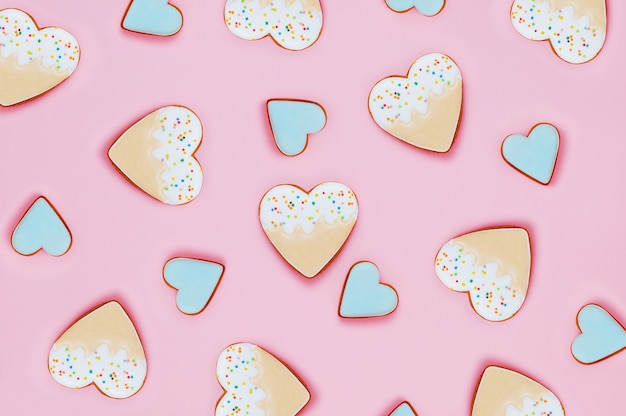 Pattern of heart shape and ice cream cookies on pink background