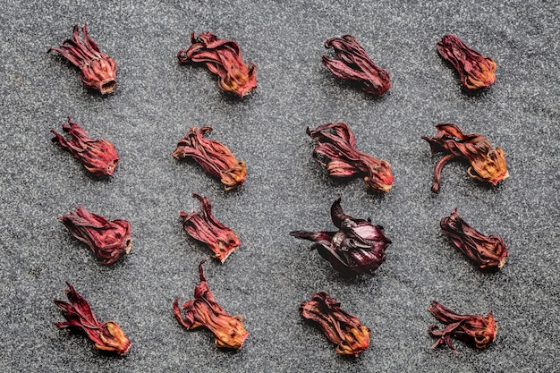 Pattern of hibiscus dried flowers (roselle, karkade) and one fresh on black stone background.