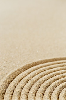Pattern in japanese zen garden with close up concentric circles on sand for meditation
