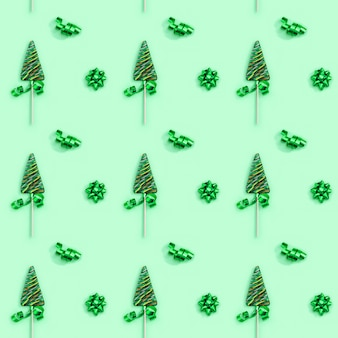 Pattern of lollipops shaped like christmas tree on green surface