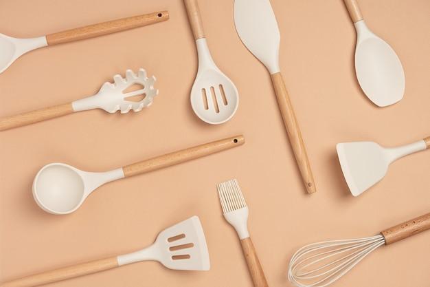 調理器具セットから作られたパターン。ベージュの背景に木製のハンドルが付いたシリコンキッチンツール。上面図フラットレイ。