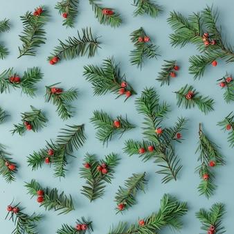 Узор из веток елки и красных ягод на синей стене. рождественское понятие. плоская планировка.