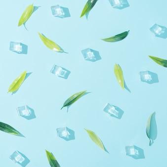 파스텔 블루에 녹색 잎과 얼음 조각으로 만든 패턴입니다. 최소한의 여름 자연 평면 평신도 구성.