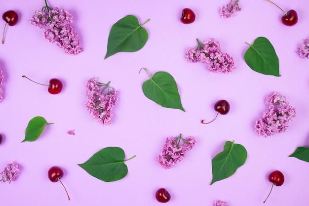 라일락 꽃, 잎 및 자주색 배경에 체리로 만든 패턴