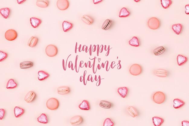 淡いピンクの背景にマカロンとキャンディーで作られたパターン。甘いコンセプト。フラットレイ、上面図