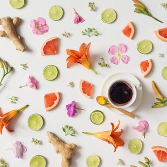 白いテーブルの上にコーヒーカップをきれいに並べた、さまざまな自然物で作られたパターン。
