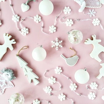 Pattern made of white christmas decoration with christmas glass balls, tinsel, bow, elk, bird on pink background.