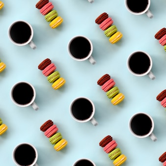 A pattern of many colorful dessert cake macaroon and coffee cups on trendy pastel blue background top view