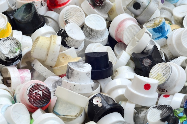 A pattern of many used and soiled nozzles from spray cans with aerosol paint.