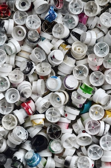 A pattern of many used and soiled nozzles from spray cans with aerosol paint