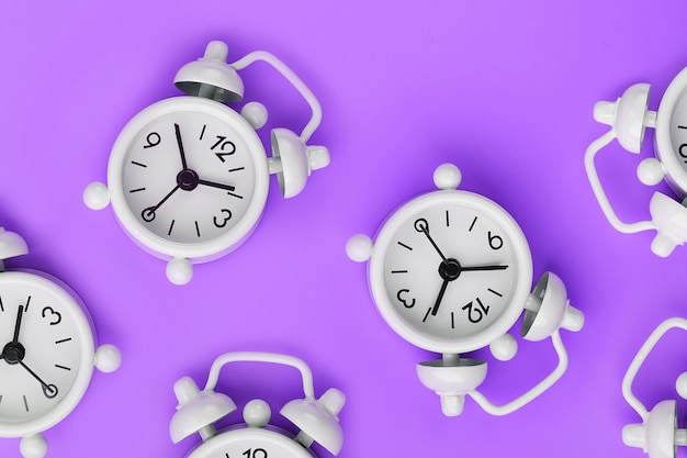 A pattern of many white classic alarm clocks in the form of a pattern on a purple background. top view with a copy of the space, flat lay.