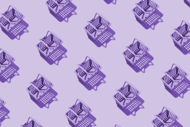 Pattern miniature shopping basket in a supermarket in purple tint. minimalistic copy space shopping concept.