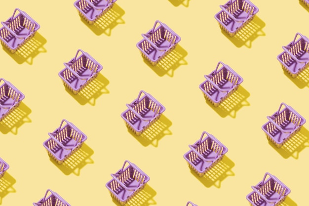 Pattern miniature shopping basket in a supermarket on a yellow background. minimalistic copy space shopping concept.