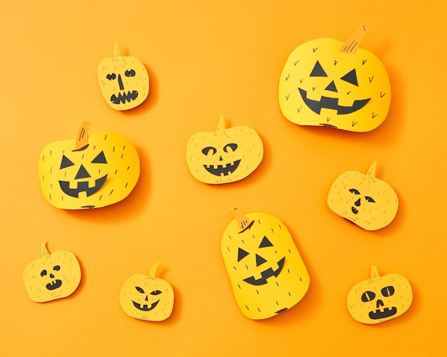テキスト用のスペースとオレンジ色の背景に顔を持つさまざまな手作りの紙カボチャのパターン。ハロウィーンへのレイアウト。フラットレイ