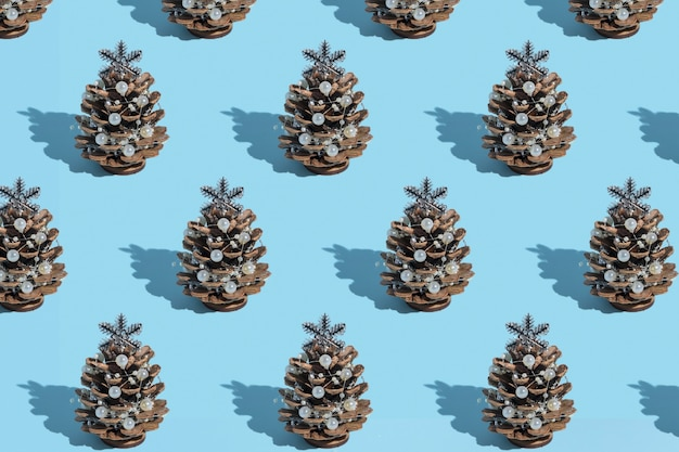 새 해 카드 하드 그림자와 파란색 배경에 구슬과 소나무 콘으로 만든 대체 새 크리스마스 트리의 패턴