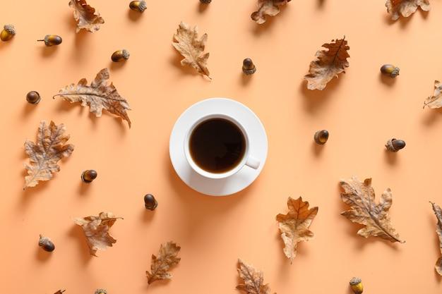 ベージュのテーブルの周りのブラックコーヒーと秋のどんぐりのパターン。上からの眺め。コンセプト代替カフェイン。