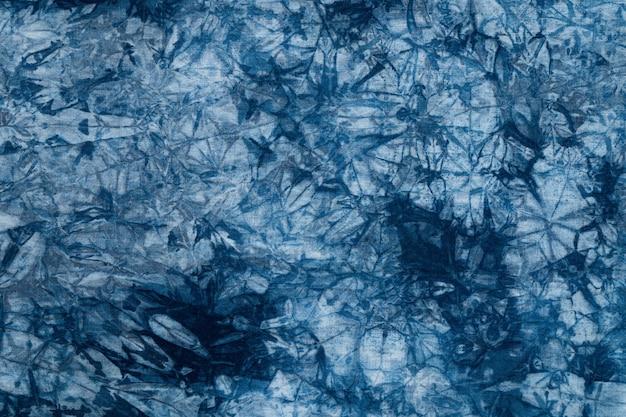 Шаблон синей краски на хлопчатобумажной ткани, окрашенный фон ткани индиго и текстурированный