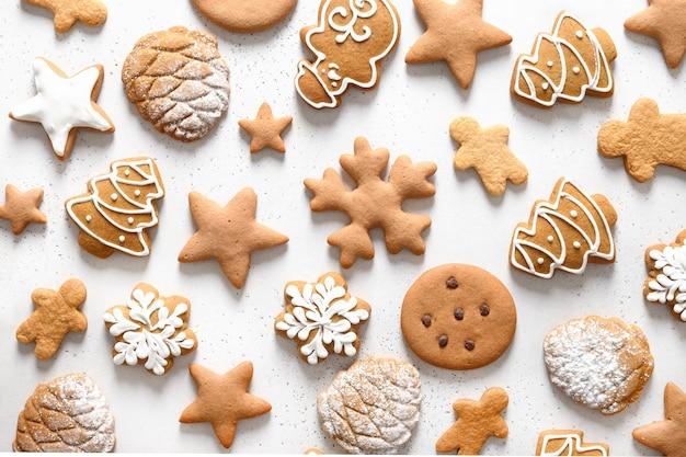 雪片、星、白いテーブルの上のクリスマスツリーなどのさまざまなクリスマス自家製艶をかけられたクッキーのパターン。クリスマスの抽象的な背景。