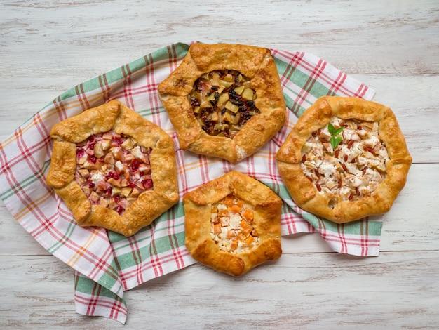 Картина различных ручных пирогов на белом деревянном столе.
