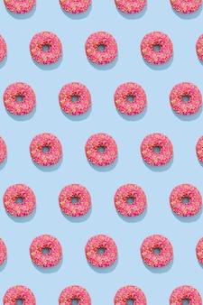 青い背景にカラフルな振りかけるピンクの釉薬のドーナツのパターン