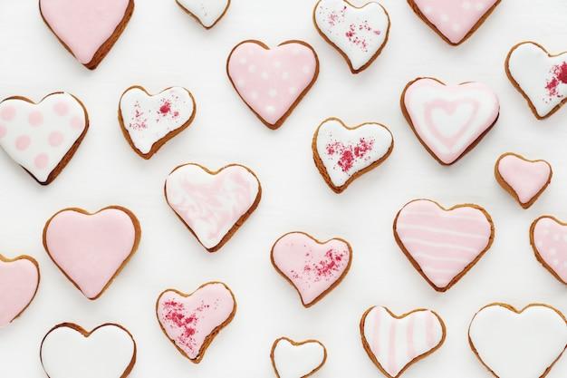 Узор из пряников в форме сердца украшен белой и розовой глазурью на белой деревянной поверхности