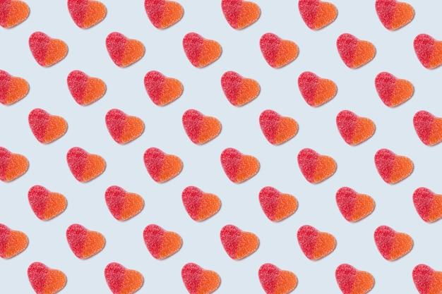 水色の背景にグミの心のパターン。バレンタインデーのコンセプト。おいしいゼリー菓子。上面図。