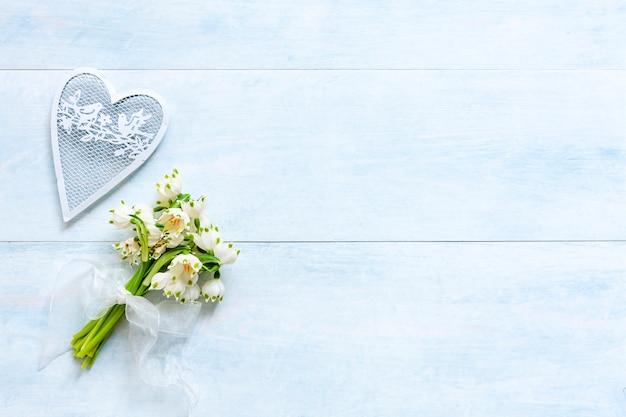 ユリのスノードロップの花と白いハート形の置物のパターン
