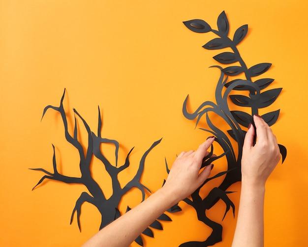 Шаблон из бумажных листьев и ветвей деревьев. руки девушки составляют композицию ручной работы на оранжевом фоне с местом для текста. концепция хэллоуина. плоская планировка