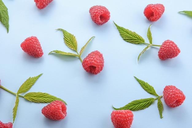 Шаблон из малины и зеленых листьев на синем фоне. плоские лежат летние ягоды - малина красная. креативный минимализм.