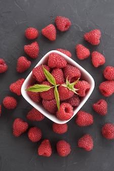 Узор из малины на темном фоне рок. плоские лежат летние ягоды - малина красная. вид сверху.