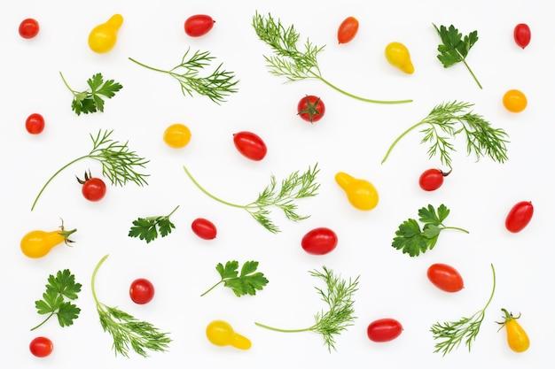 赤と黄色のトマト、グリーンパセリ、白い表面にディルのパターン
